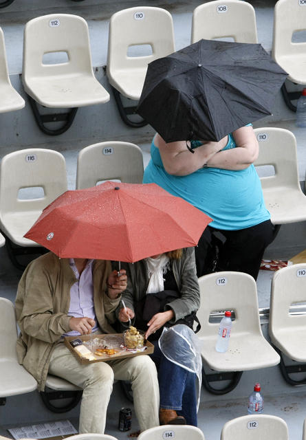 Fans protect themselves from the rain under umbrellas during France's Nicolas Devilder's match against Spain's Rafael Nadal at the French Open tennis tournament at Roland Garros in Paris