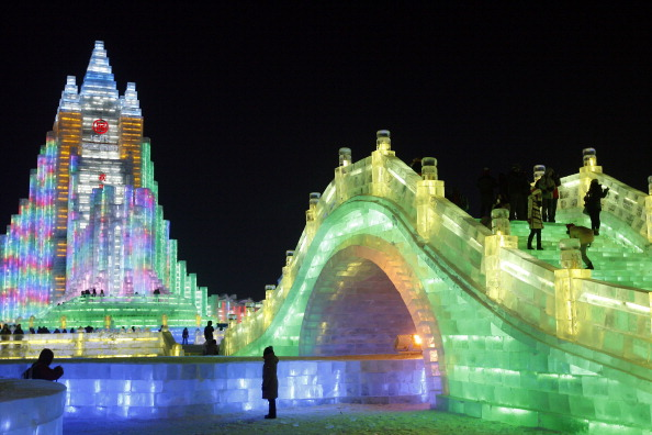 """This picture taken on December 30, 2013 shows people visiting the ice lanterns and carvings at the 2014 Harbin International Ice and Snow Festival in Harbin, in northeast China's Heilongjiang province. This year's """"Ice and Snow World"""" will officially open on January 5, 2014.       CHINA OUT         AFP PHOTO        (Photo credit should read STR/AFP/Getty Images)"""