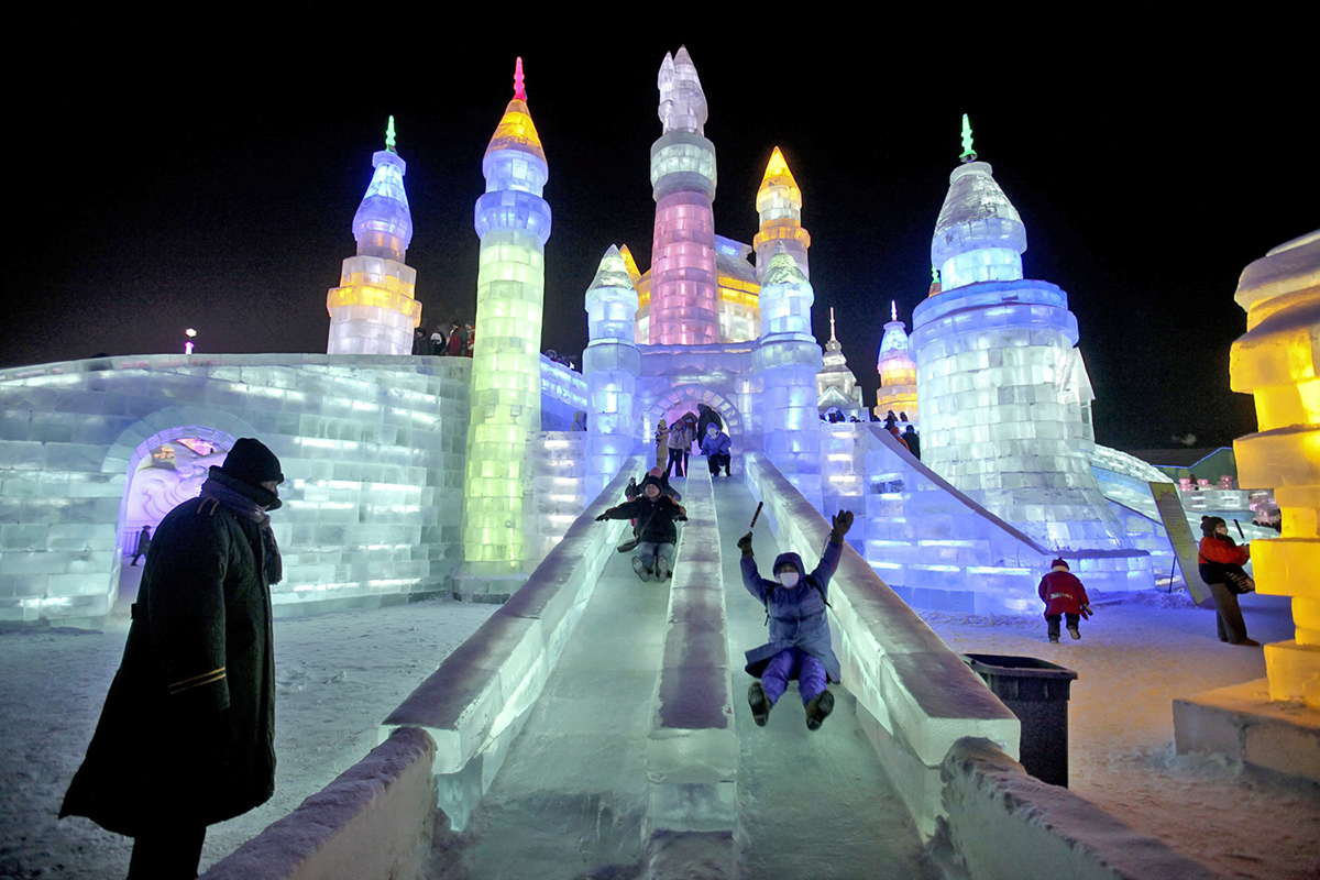 epa03525329 People slide down an ice slide at the 29th Harbin International Ice and Snow Festival in Harbin, China's northern Heilongjiang province, 05 January 2013. The three-month-long subzero festival is ints 29th edition, attracting both foreign and local visitors.  EPA/DIEGO AZUBEL